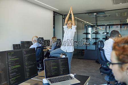 woman practicing yoga in office surrounded