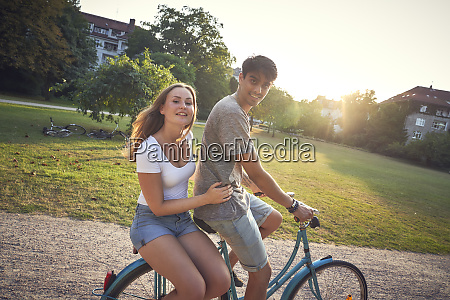young couple riding bicycle in park