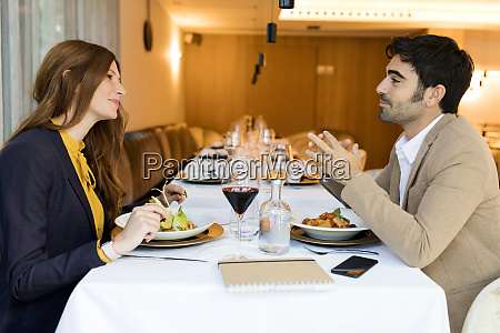 smiling man and woman eating in