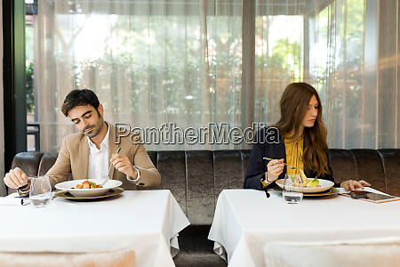 man eating and woman using tablet