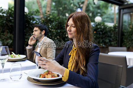 man and woman using cell phones