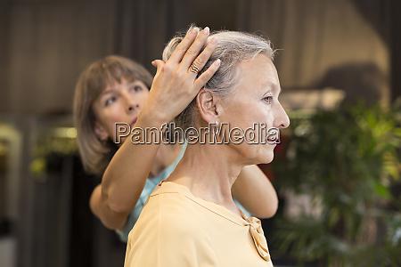 frau hilft seniorin mit ihren haaren