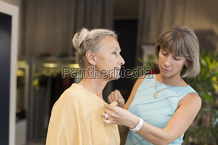 shop assistant helping senior woman in