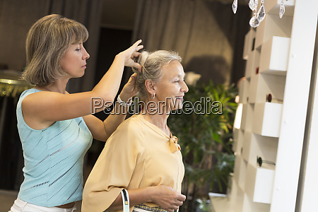 woman helping senior woman with her