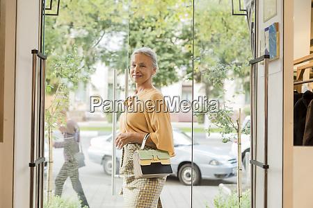 laechelnde seniorin die eine boutique entlanggeht