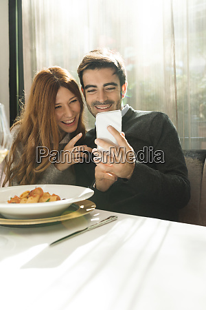 happy couple looking at cell phone