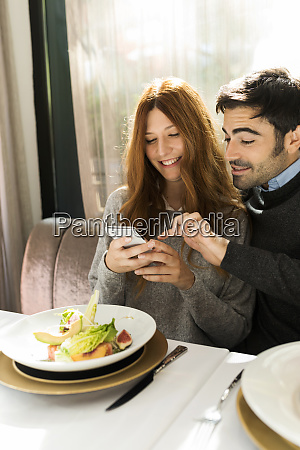 happy couple using cell phone in