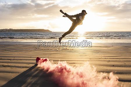 mann macht bewegungstraining am strand mit
