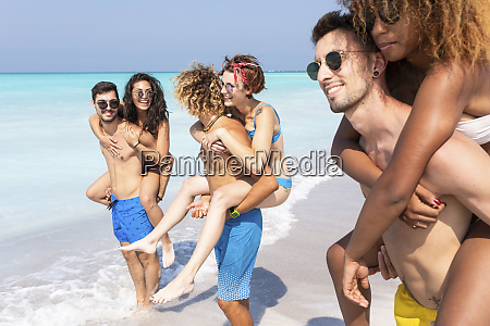 friends walking on the beach carrying
