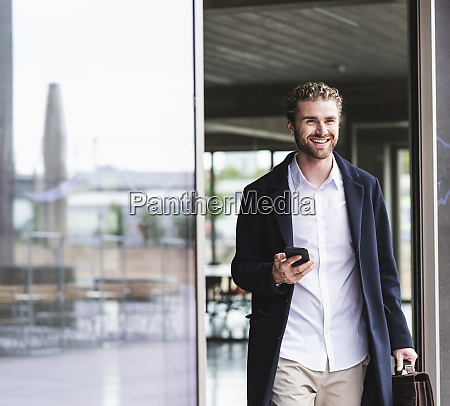 smiling young businessman holding cell phone