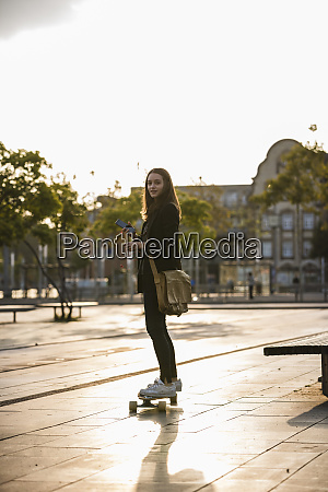 young woman with cell phone riding