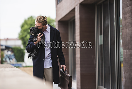 young businessman cuddling dog outside office