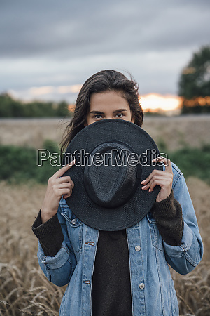 portrait of young woman hiding behind
