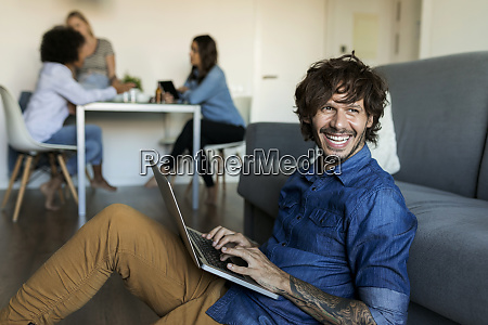 laughing man sitting on floor using