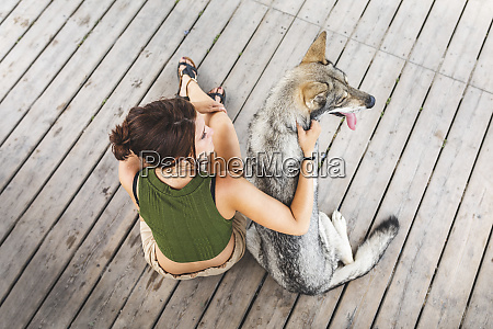 young woman sitting besides her dog