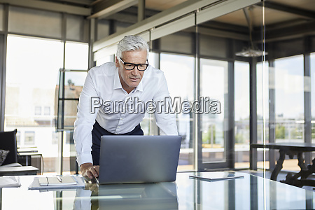 businessman standing at desk looking at