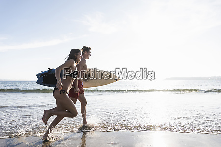 france, , brittany, , young, couple, with, surfboard - 26403685