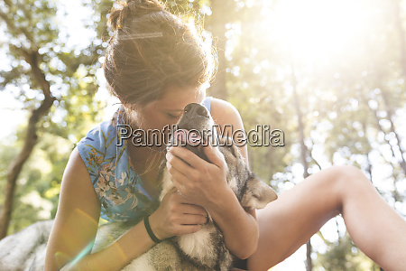 young woman cuddling her dog in