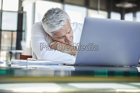 exhausted businessman sleeping in front of
