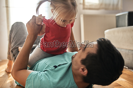 little girl playing with her father