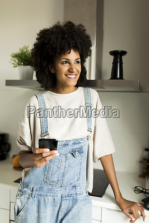 smiling woman holding cell phone in