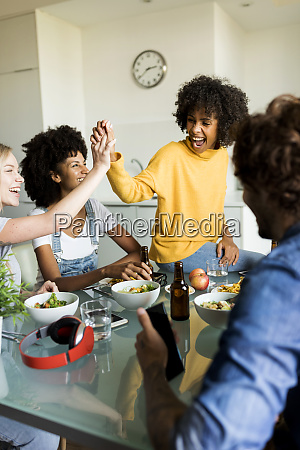 cheerful friends sitting at table talking