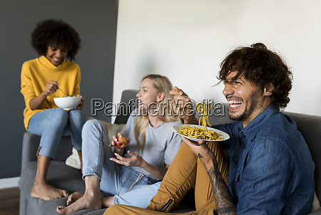 cheerful friends sitting on couch talking