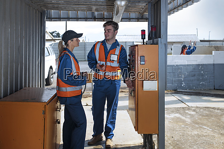 two workers wearing overalls and reflective