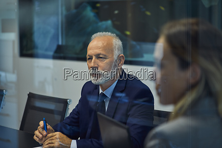 portrait of senior businessman listening in