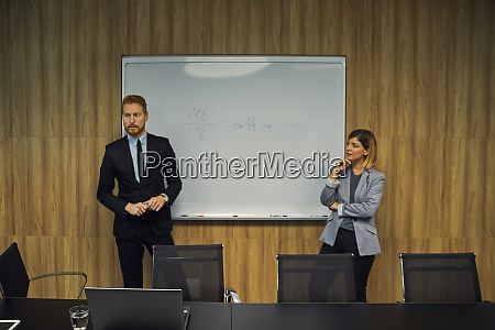 businessman and businesswoman leading a presentation
