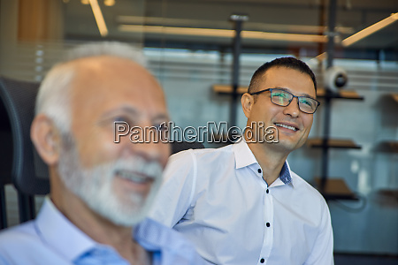 two smiling businessmen in office