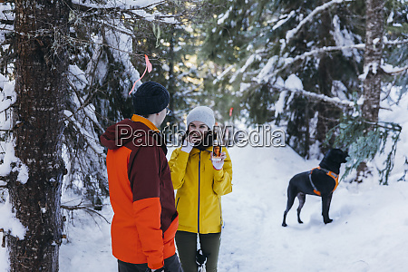 couple with dog in forest in