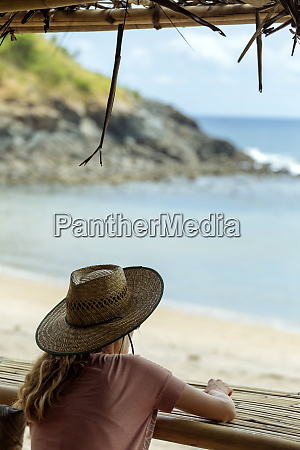 rearview offemaletourist in straw hat looking