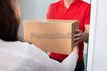 woman taking box from delivery man