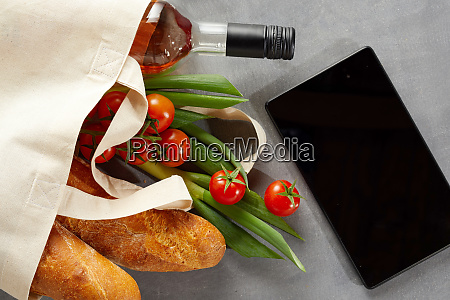 tablet with fresh groceries in reusable