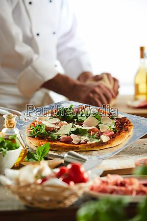 chef wuerzt eine pizza in einer