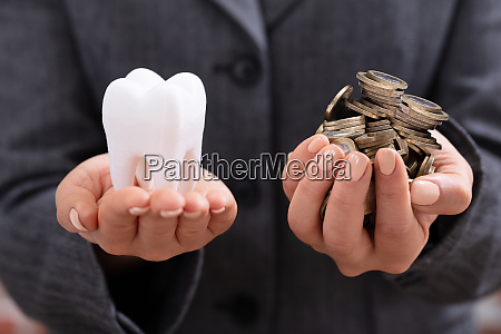 frau holding zahn und muenzen