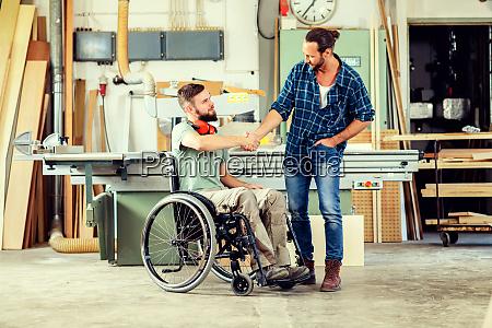 arbeiter im rollstuhl in einer schreinerwerkstatt
