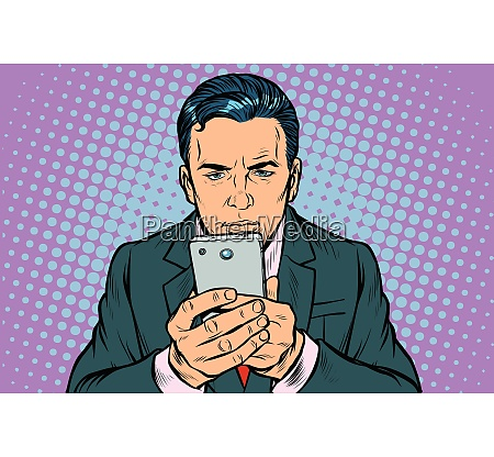 man looks at the smartphone