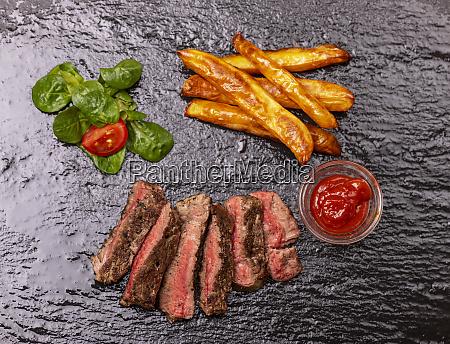 scheiben steak mit pommes auf schiefer