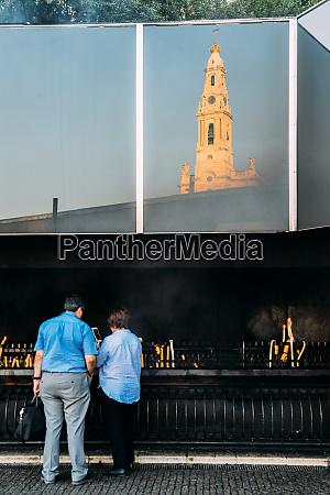 religious pilgrims light candles at sanctuary