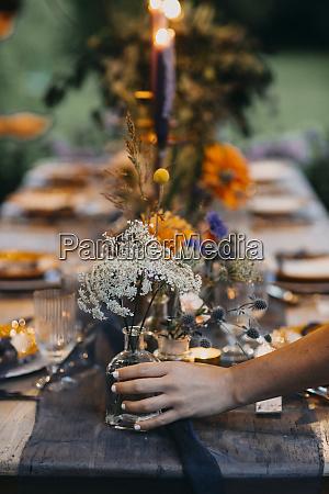 hand placing flower vase on festive