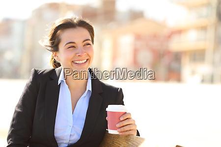 glueckliche geschaeftsfrau schaut weg auf kaffeepause