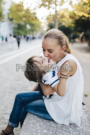 mother sitting on bench cuddling with