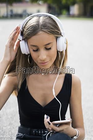 relaxed teenage girl wearing headphones listening