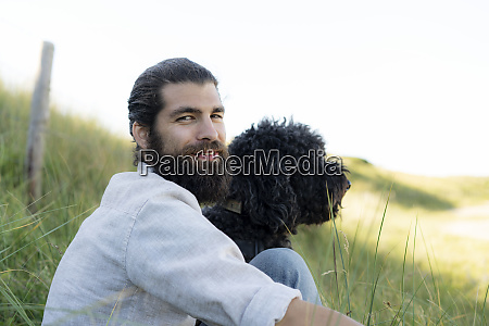 young man sitting in the dunes
