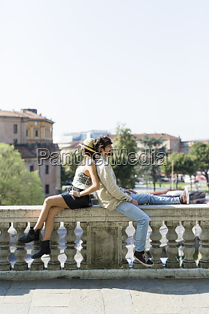 young couple relaxing back to back