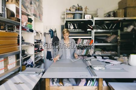 modedesigner arbeitet an vorlage im studio
