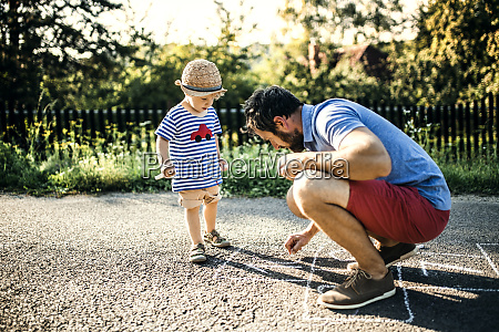 father drawing hopscotch on asphalt while