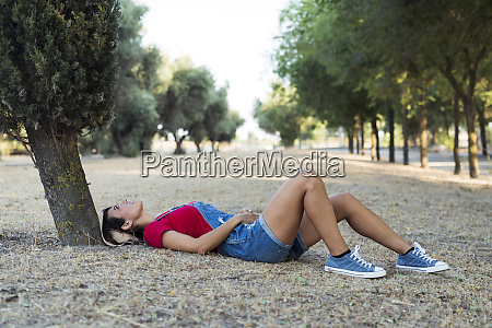 woman lying on ground in nature